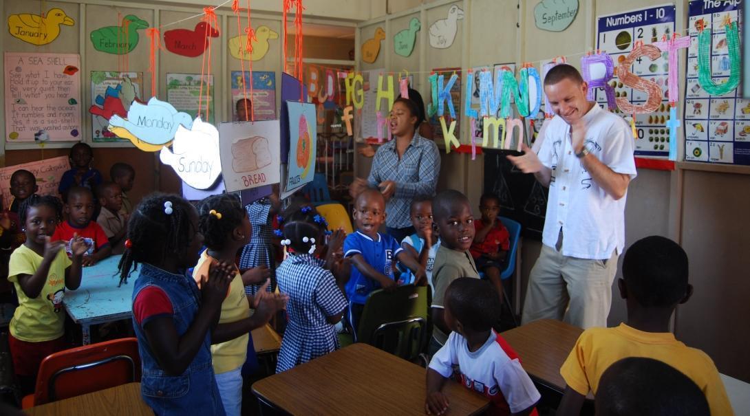 Voluntario de educación en Jamaica canta y baila con sus estudiantes durante actividad didáctica.